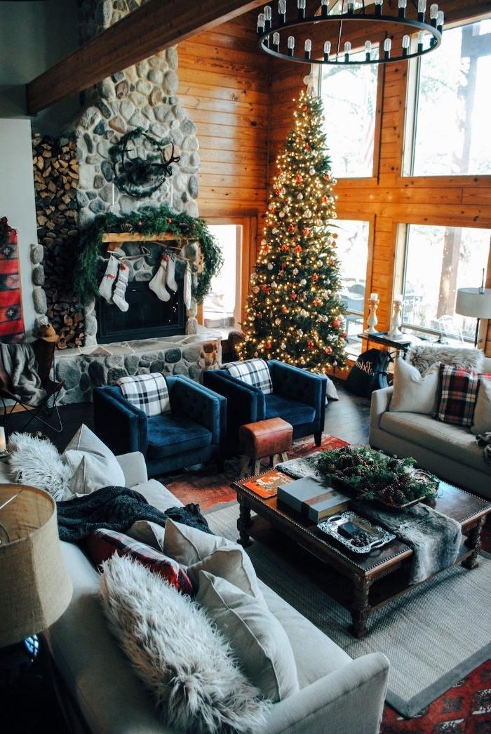 grande cheminée rustique de pierre fauteuils bleu foncé canapé gris clair table basse bois grandes fenetres sol parquet foncé