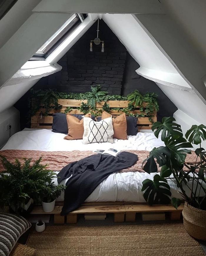 idée déco chambre parentale sous plafond mur briques noires lit palette recyclée tapis beige cache pot tressé plantes chambre