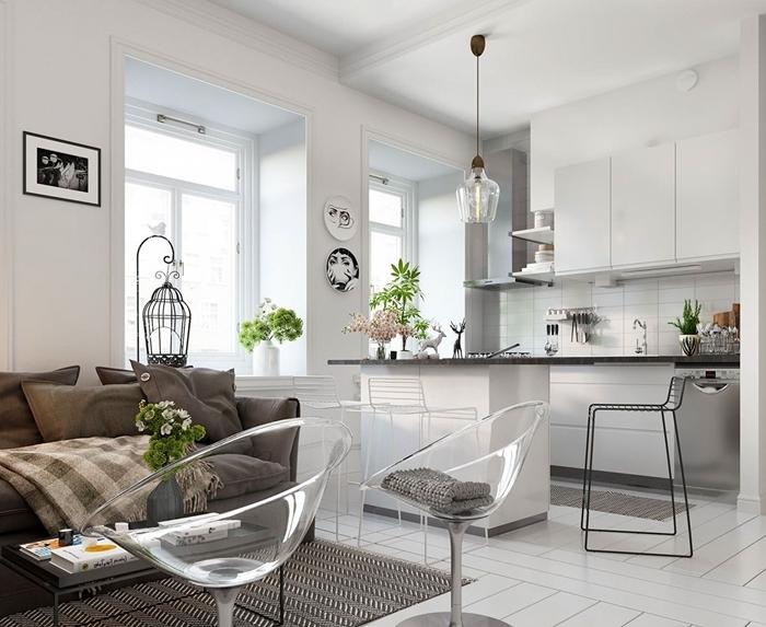 idée petite cuisine minimaliste avec crédence blanche îlot comptoir gris chaises transparentes canapé coussins décoratifs