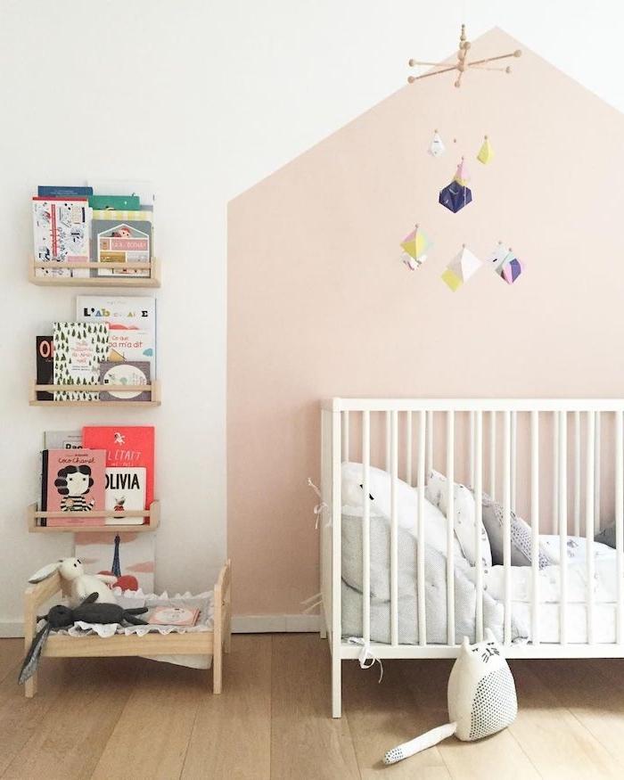 idée déco chambre bébé mur rose pale lit blanc à barreaux parquet bois étagères bois avec des livres enfant exposés