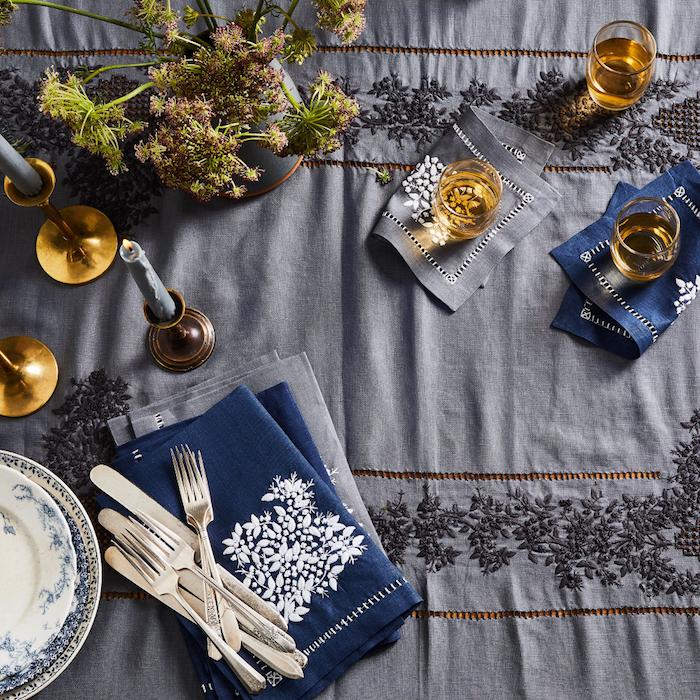 idee deco table noel avec des couvertes argentines nappe bleu avec des broderies assiettes en porcelaine
