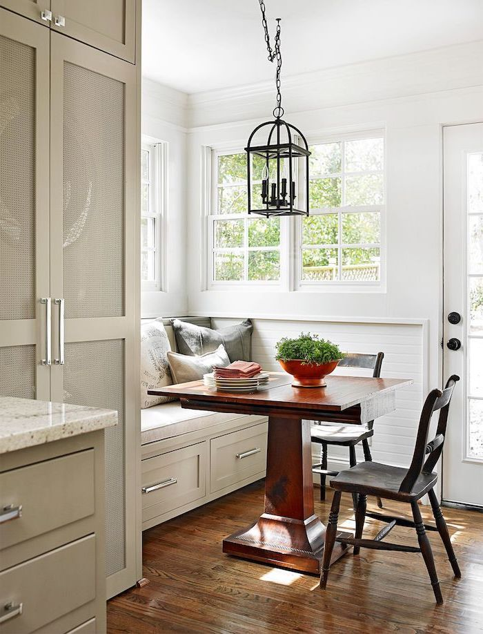 ilot central avec coin repas compose d une banquette deux chaises et table en bois des murs blanc