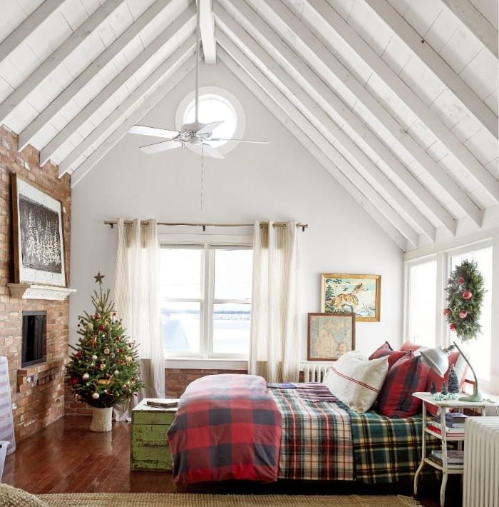 interieur chalet deco chambre cocooning linge de lit à carreaux parquet bois repeint sapin de noel décoré bout de lit coffre cheminée briques poutres apparentes blanches