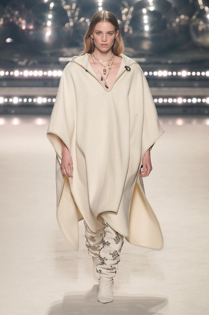isabel marant tendance hiver 2021 poncho en couleur blanc fonce avec des bottes et un colier extravagant