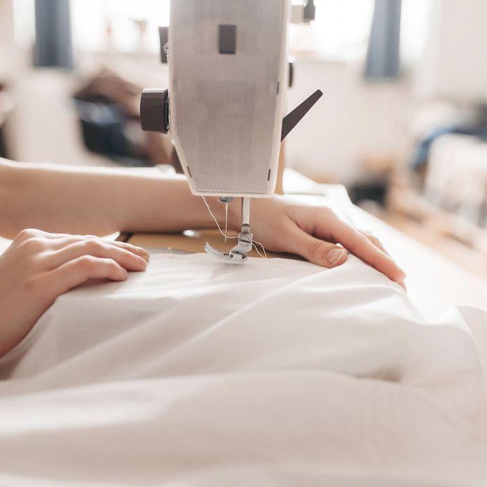 le proces de coudre un tissu ddes main de femme et une machine a coudre un tissu blanc