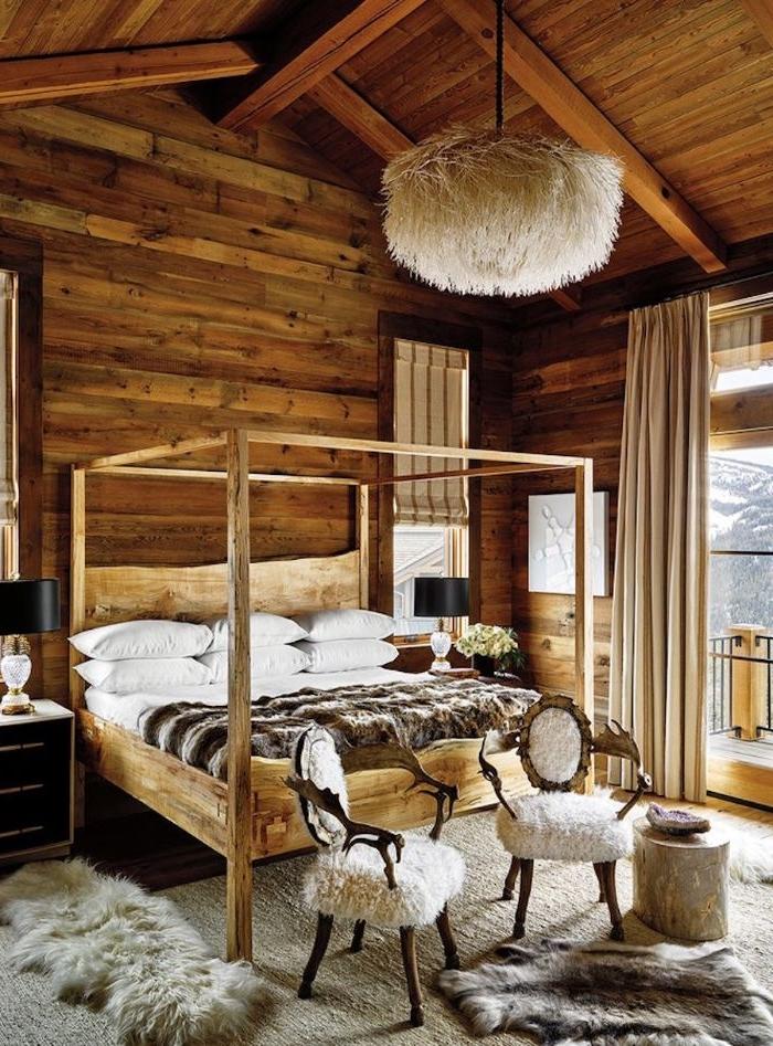 lit baldaquin bois murs et plafond bois brut tabourets bois et fourrure tapis faurroure table touret