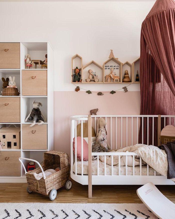 chambre bébé cocooning, lit blanc à barreaux avec ciel de lit bordeaux peinture murale blanche et rose rangement meuble bois chambre cocooning fille deco