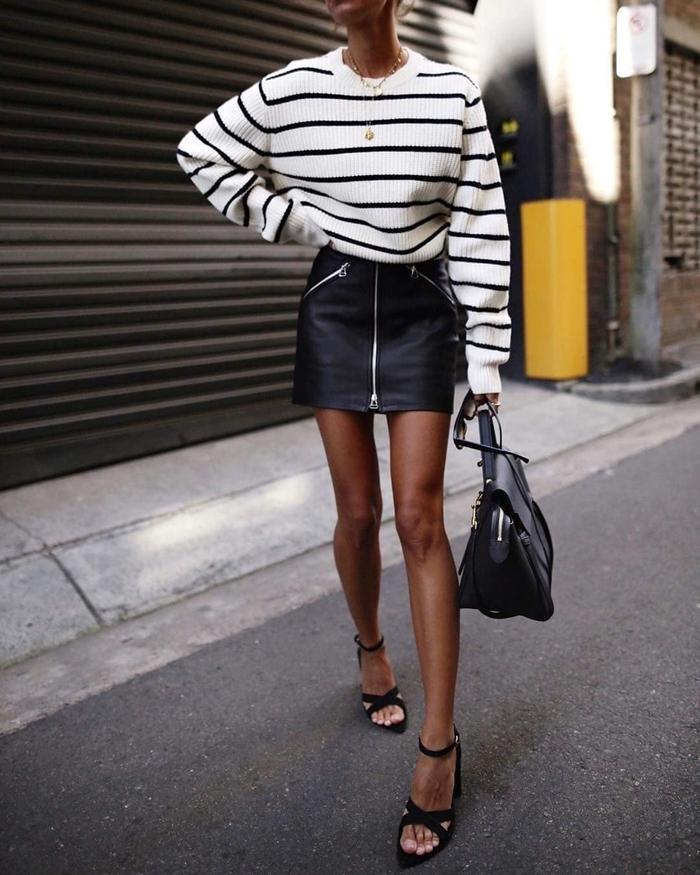 look jupe cuir fermeture éclaire taille haute pull oversize blanc rayures noires collier or sac à main noir sandales talons
