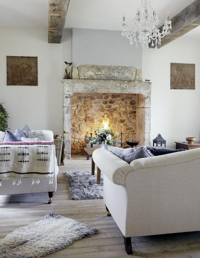 lustre elegant à mapilles canapés blancs décorés de coussins cocooning tapis moelleux cheminée de pierre table basse bois avec deco nature