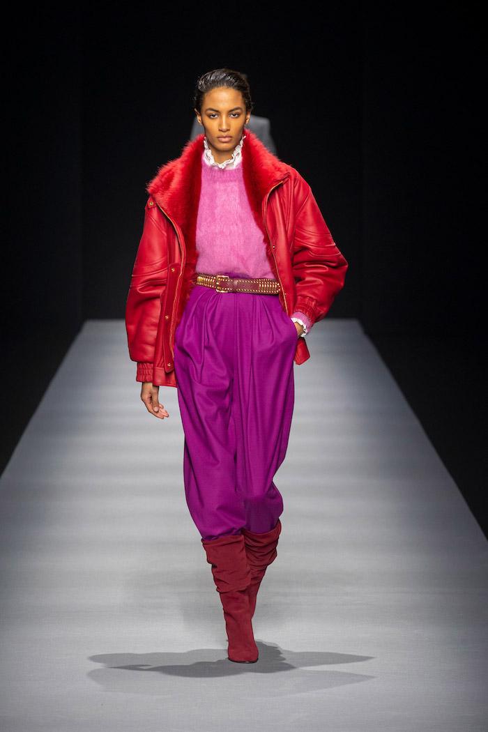 mannequine sur le podium en pantalon rose taille haute avec une veste et bottes rouges colle blanche idee tenue soiree simple