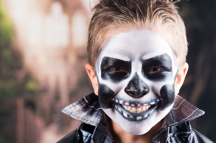 45443232 scary little boy smiling wearing skull makeup for halloween