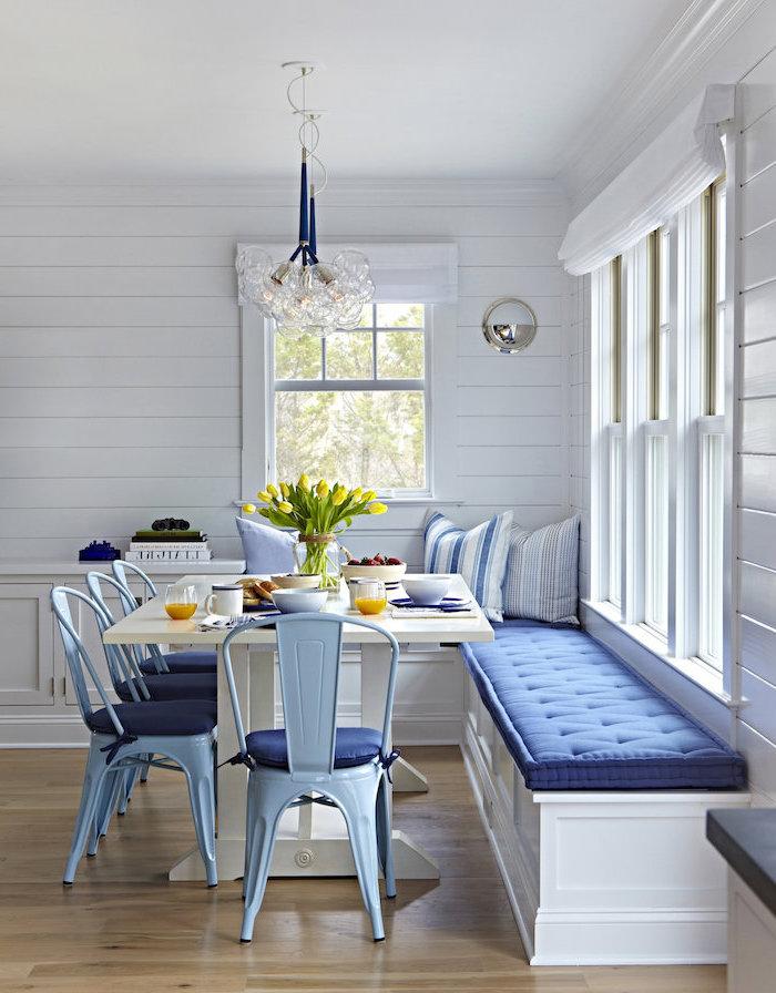 meubles de cuisine et de salle a manger couleurs predominants bleu et blanc une table et quatre chaises