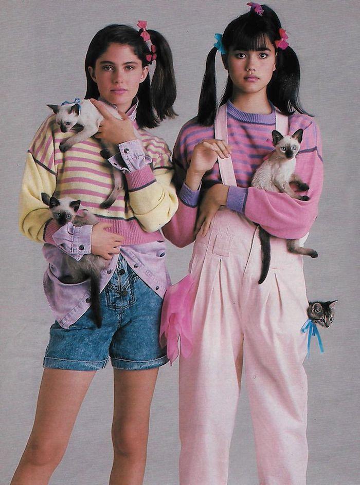 mode année 80 deux filles avec une salopette et des shorts en jean trois chats et des cheveux en queues
