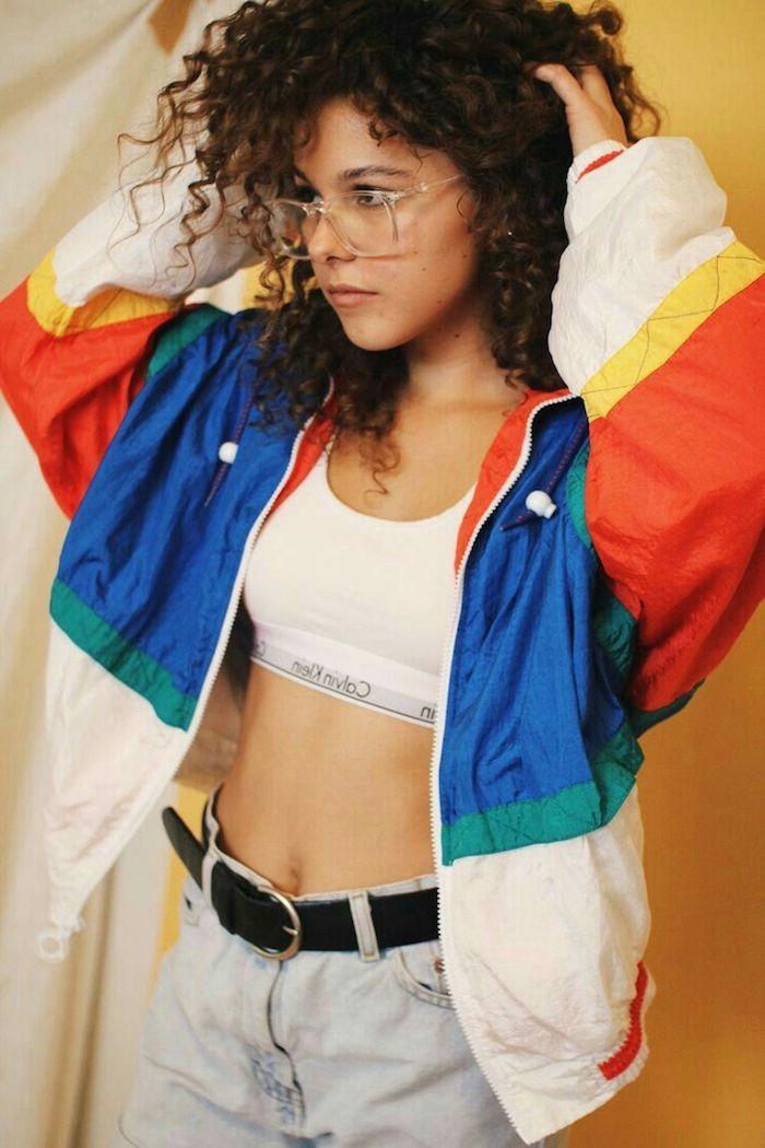 mode année 80 top courte blanc des jeans claires taille haute et un survetement sportif une fille avec des lunettes