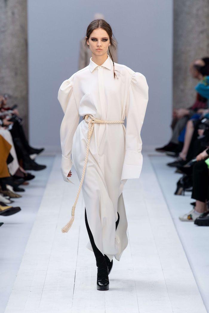 mode automne hiver 2020 une robe chemisier aux manches logues blanche et surdimensionnee avec des bottes noires