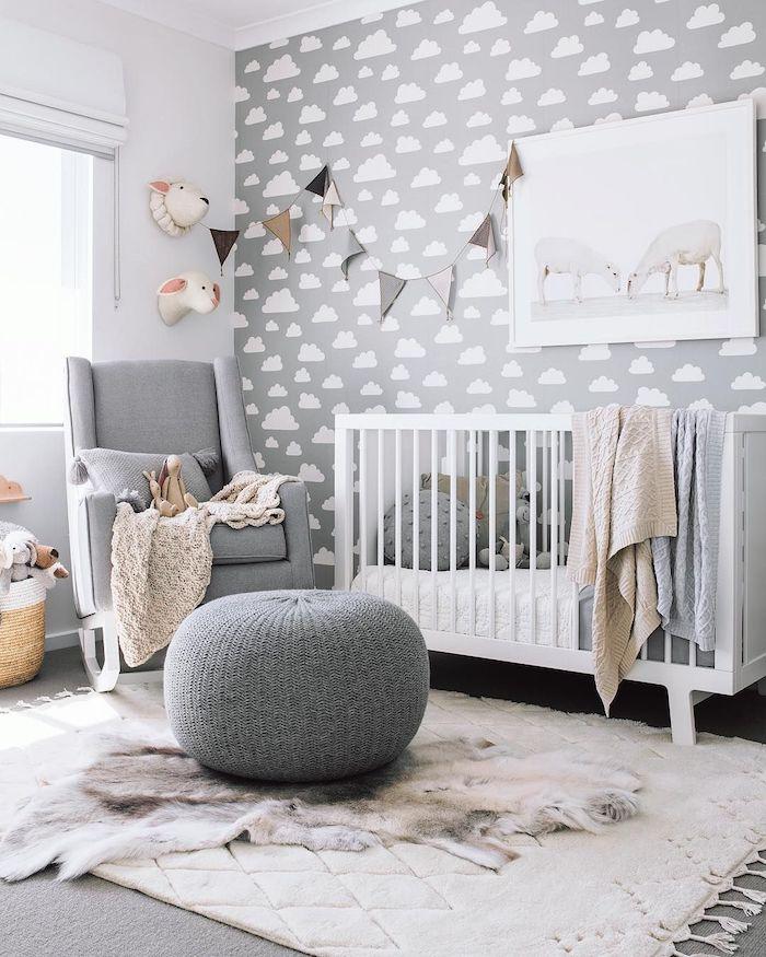 mur décoré de papier peint gris à nuages fauteuil gris lit bébé blanc tapis moelleux pouf cosy idée déco chambre bébé garçon