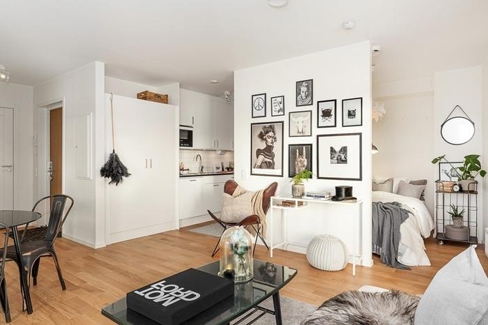 mur de cadres photo blanc et noir amenagement petit espace déco coin cuisine blanche parquet bois table à manger noir verre