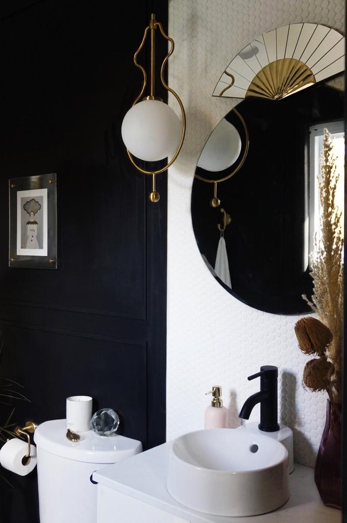 mur noir miroir rond accents laiton idée salle de bain moderne de style retro chic évier rond blanc robinet noir mat