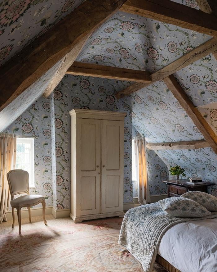 papier peint bleu motifs floraux poutres apparentes bois brut aménagement sous comble chambre adultes garde robe