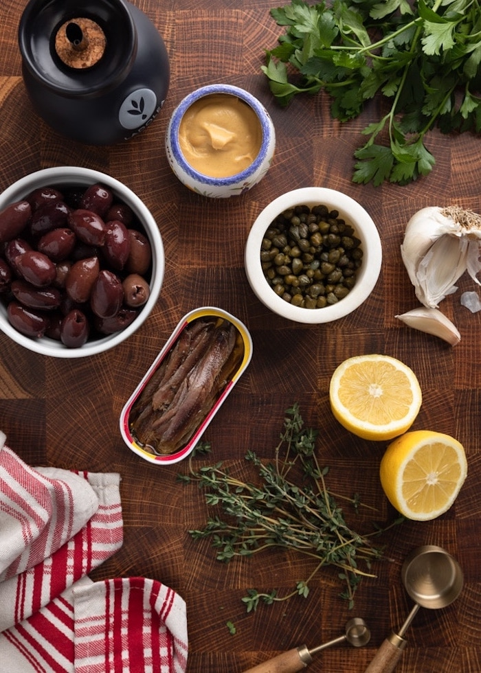 pate a tartiner mediterranee tepanade a la base d olives capres et anchois des produits sur une table nappe en noir et rouge