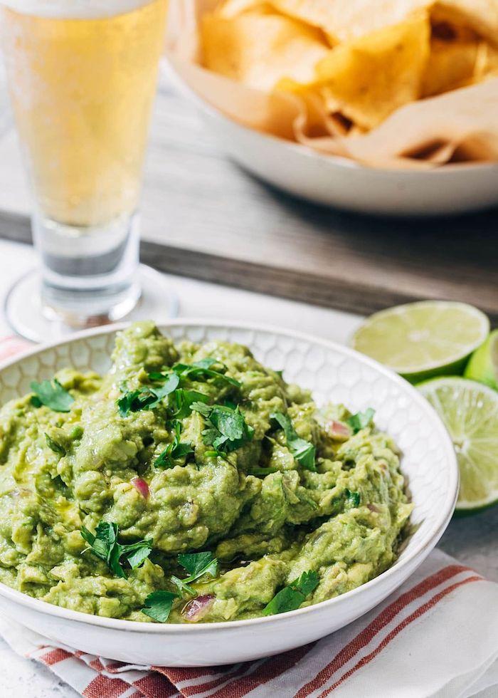 pate a tartiner recette de guacamole servi avec une pinte de biere des nachos et un citron vert coupe en demie