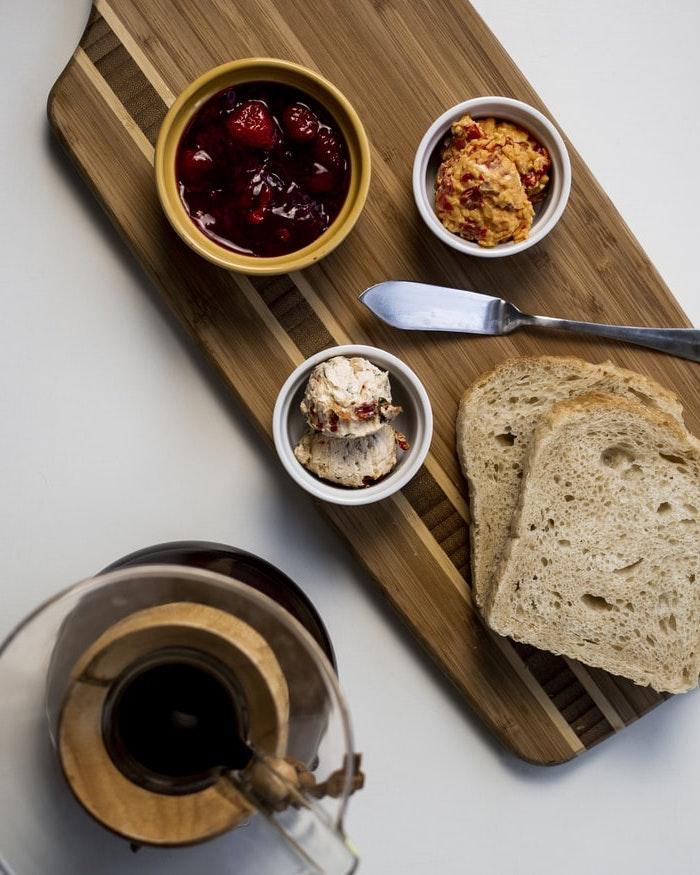 pates a tariner maison servis sur une plaque en bois avec deux tranches du pain et un broc de cafe