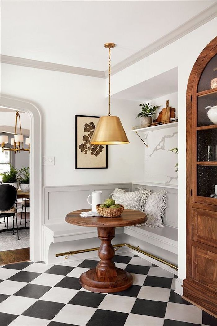 petit coin cuisine avec un banc integre et carrelage en carreaux au sol une armoire en bois a cote