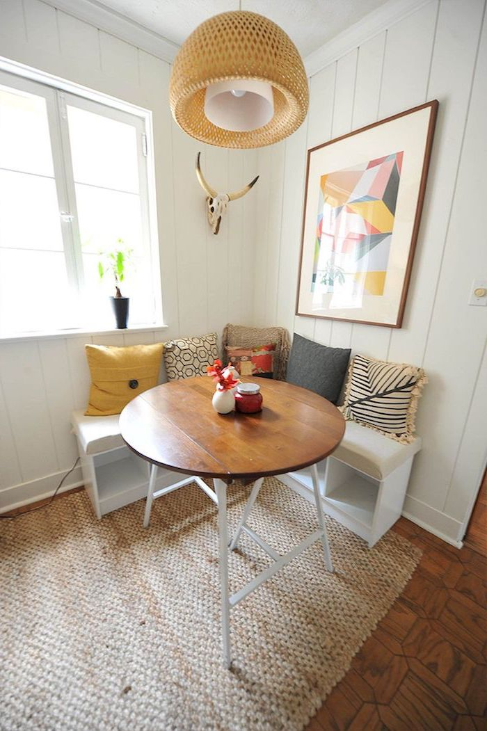 petit coin repas de cuisine avec un banc en angle et une table ronde beaucoup de coussins et un tapi ratan