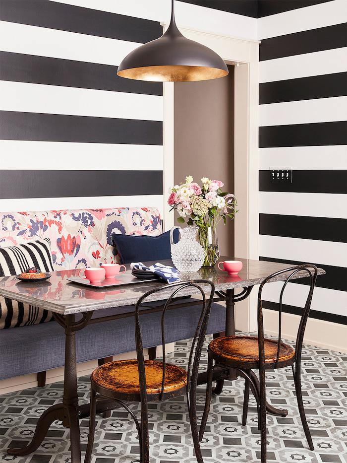 petit coin repas de cuisine avec un canape et deux chaises combinaison et contraste des motifs au sol et aux murs