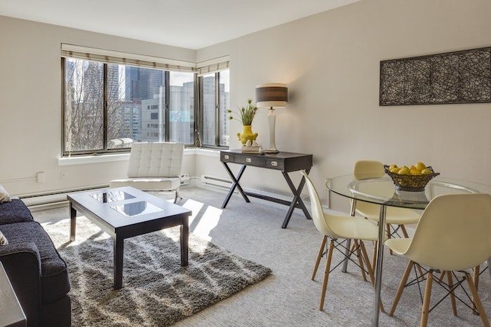 petit salon avec des grandes fenetres et un coin de repas integre petite table en verre et chaises jaunes en plstique