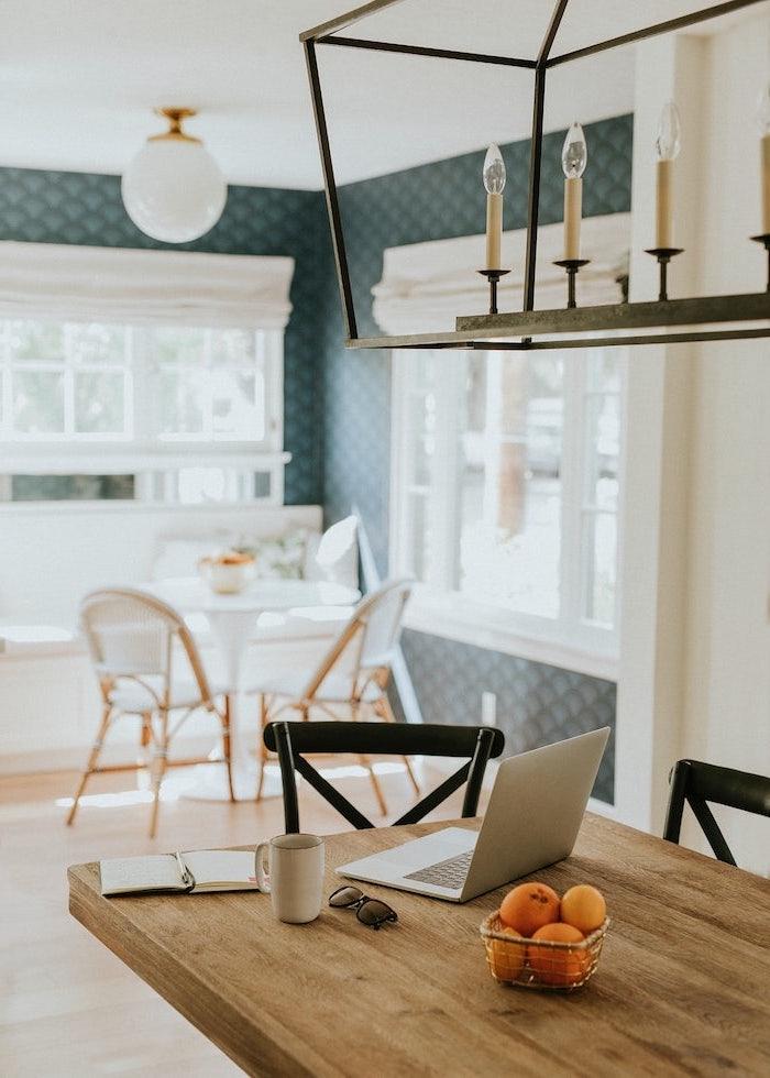 petite cuisine ouverte sur petit salon des clementines et un ordinateur sut table en bois murs en bleu fonce et sol clqire