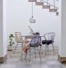 petite cuisine ouverte sur petit salon trois chaises ratan autour d une petite table de repas au dessous de l escalier