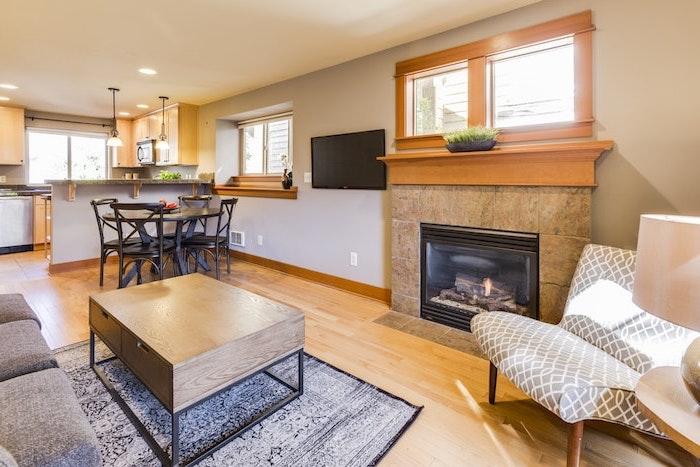 petite cuisine ouverte sur un petit salon avec cheminee et un tele