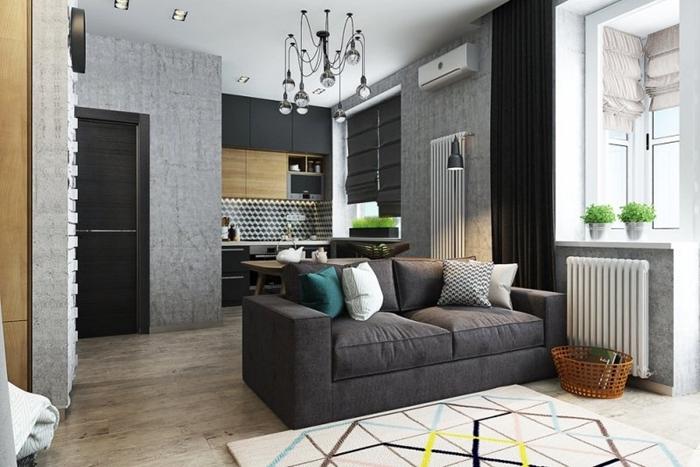 petite cuisine pour studio avec meubles haut en bois et noir mat canapé gris anthracite revêtement sol carrelage aspect bois