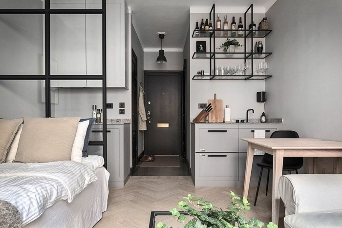 petite cuisine studio meubles bas gris clair mat étagère suspendue métal noirci table bois chaise noire plante verte