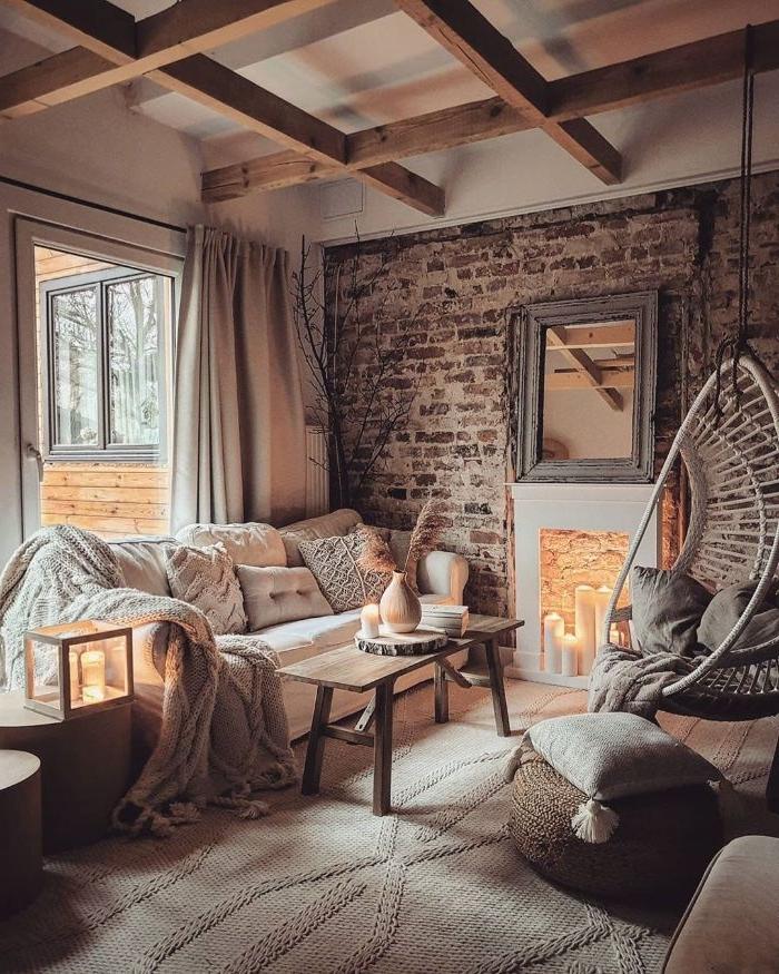 plafond de poutres apparentes canapé blanc décoré de coussins et plaids mur de briques tapis maillée pouf de rotin