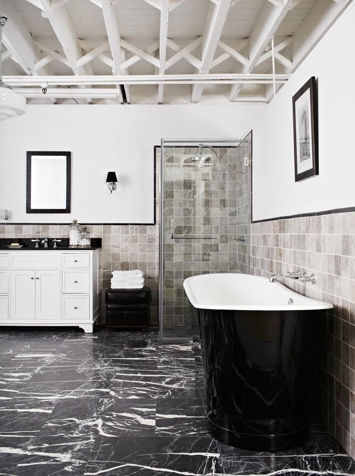 plafond poutres bois blanc apparentes salle de bain art déco cadre miroir noir baignoire noire dalles marbre noir