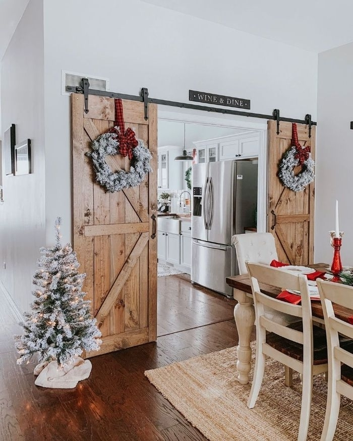 portes de grange recyclées avec decoration couronne de branches de pin table et chaises de bois cuisine blanche rustique