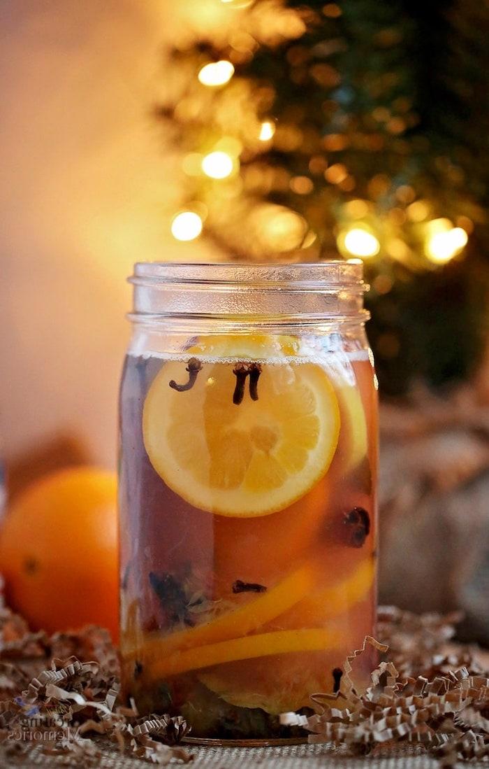 pot pourro dans pot en verre avec des tranches d orange et de citron et des épices de noel variés en eau