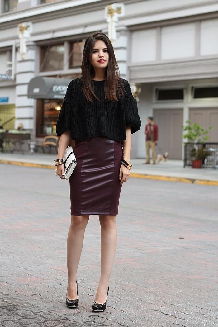 pull noir manche bouffantes jupe en cuir femme violet foncé chaussures talons noirs sac pochette blanc bracelet noir