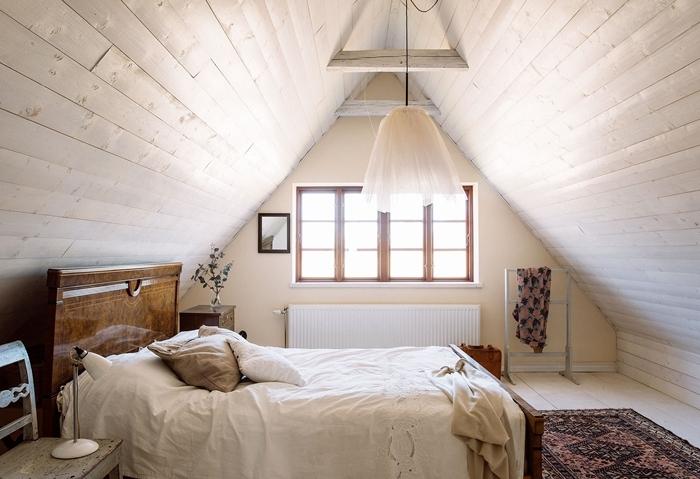 revêtement mural panneaux bois chambre sous les toits tête de lit bois foncé meuble de chevet tapis motifs ethniques
