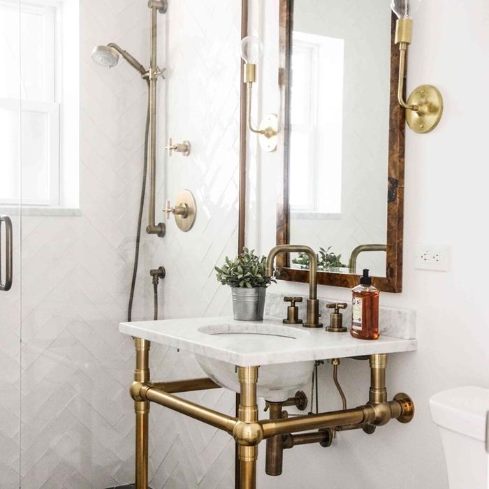 robinet métal évier sur pieds dorés salle de bain vintage revêtement mur carrelage blanc motifs géométriques miroir bois