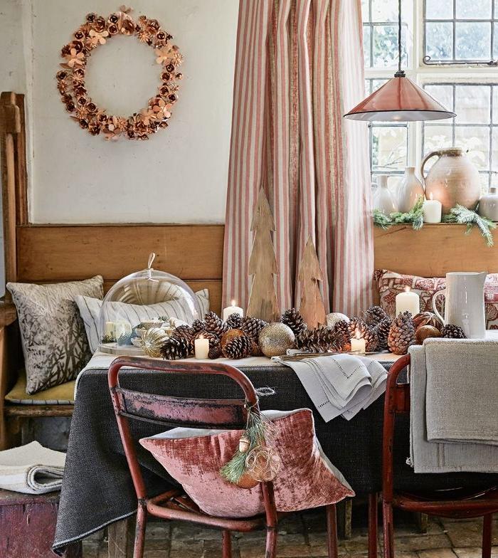 salle a manger rustique avec table décorée de nappe grise centre de table en pommes de pin et bougies chaie metal et banc de bois deco coussins