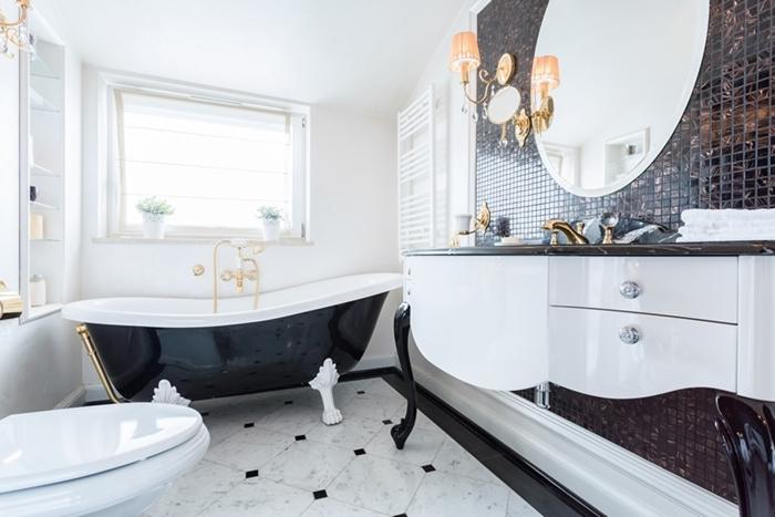 salle de bain retro chic décoration intérieure style antan luxe baignoire noir brillant accents laiton carrelage marbre