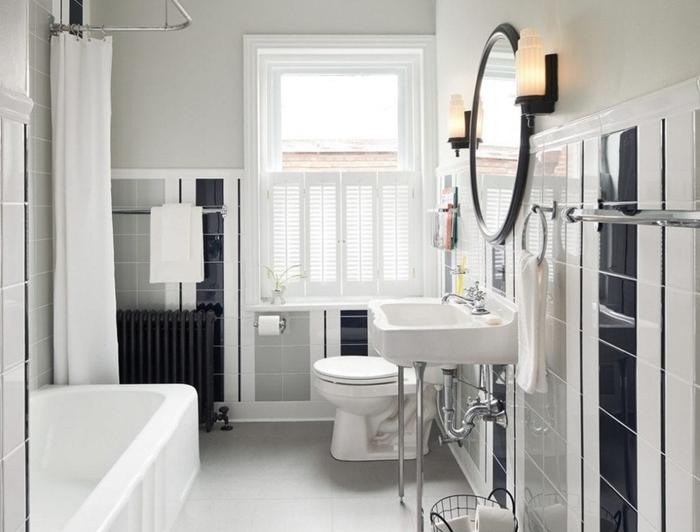 salle de bain style ancien avec baignoire rideaux blancs évier sur pieds métal miroir rond noir carrelage noir
