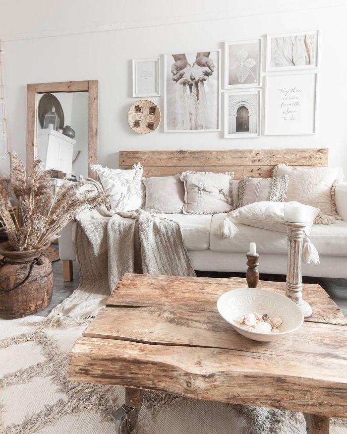 salon blanc et bois avec table basse de bois canapé bois et coussin blanc tapis à franges deco murale de cadres ambiance scandinave