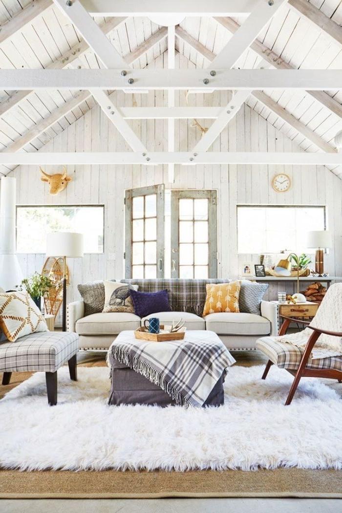 salon lanc style ferme avec ossature apparente canapé gris fauteuils à carreaux tapis blanc cocooning table basse grise tabouret
