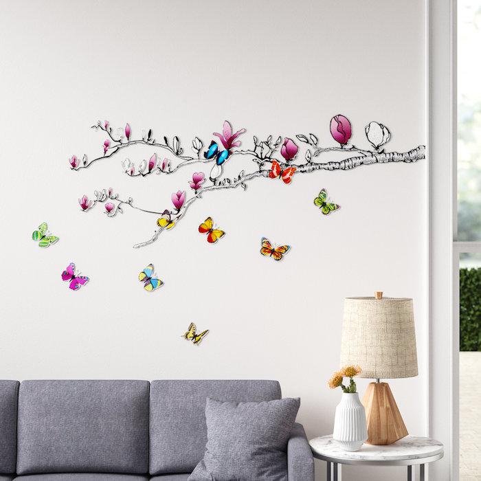 sticker mural dessin branche de mangolia avec des papillons pour la salle de sejour avec un canape gris