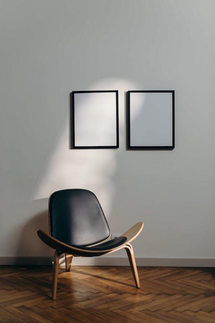 stylistique neutre et minimaliste teux tableaux blanches au mur sol en parquet et un fauteil en cuir noir