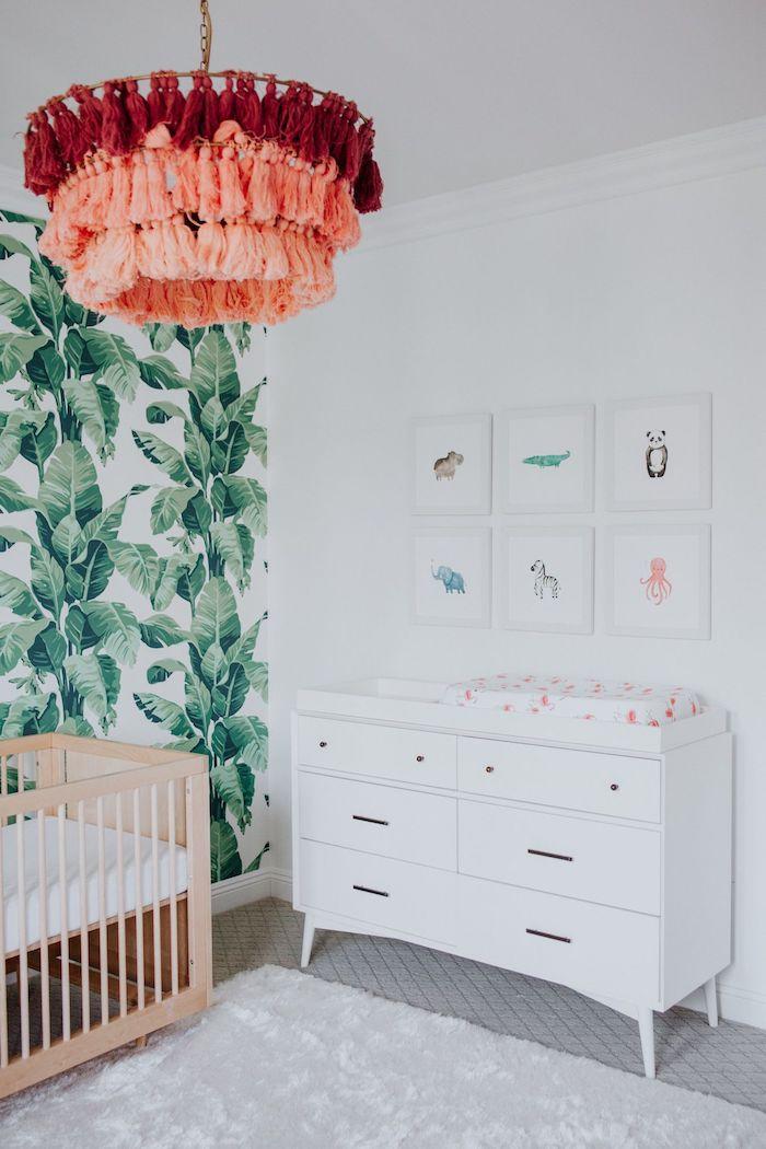 suspension à pompons à franges papier peint jungle deco murale de dessins encadrés commode blanche lit bois à barreaux